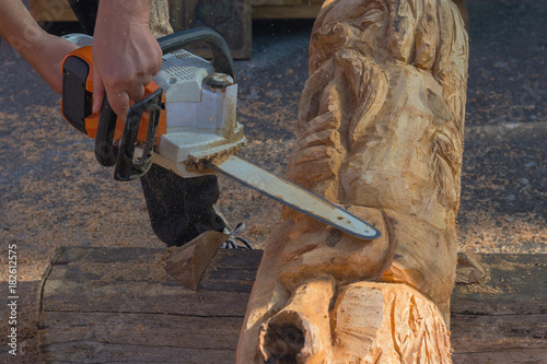 Master's hands with the saw plant sculpture from a tree. Art