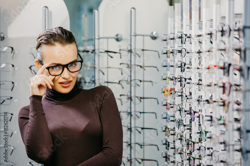 edd1216d504 Woman with Eyeglasses in Optical Store - Beautiful girl wearing glasses in optician  shop. Ophthalmology.