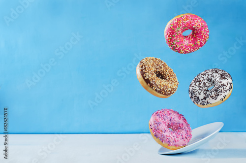 Photo  Flying multicolored donuts with plate