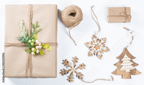 classy christmas gifts box presents in brown paper with toys and new year decor on white