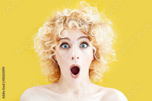 Fotografija  Surprised curly blonde girl with excited face looking at the camera with mouth o