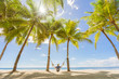 Tourist in hat sitting on hammock on the beach between palms. Travel and vacation concept.