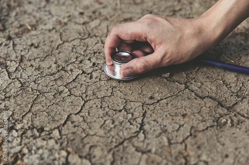 Broken soil and stethoscope concept of world with pollution. Fotobehang