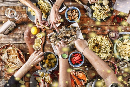 Christmas dinner. Falling golden snowflakes. Cheers Top of view of a nicely served wooden table Christmas dinner with tasty dishes and snacks, friends are toasting with glasses of red and white wine
