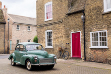 Retro Scene With Vintage British Car 1950 Style Parked In Front Of Victorian English Building With Red Door.