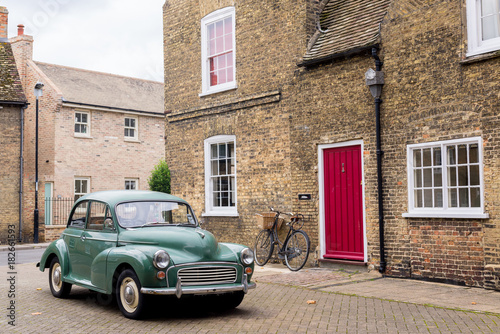Foto op Canvas Vintage cars Retro scene with vintage British car 1950 style parked in front of Victorian English building with red door.