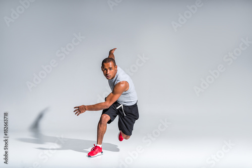 Photo young african american sportsman running and looking at camera on grey