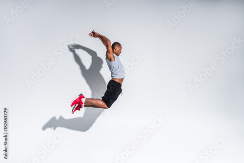 Fotografia side view of young african american sportsman jumping on grey