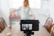 Defocused photo of a blogger's florist recording to the camera a master class for making a bouquet of pink flowers. Focus on the camera