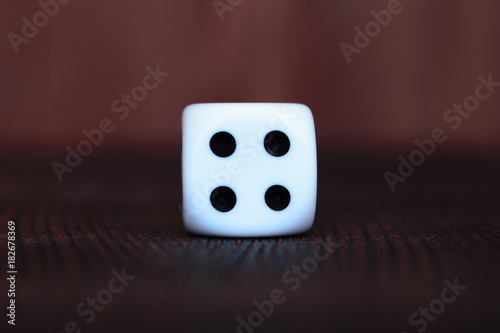 Single white plastic dice on brown wooden board background плакат