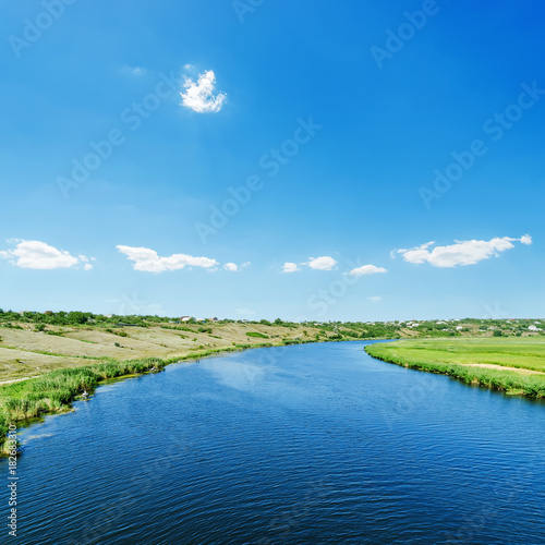 Poster Blauw blue river in green landscape and sky with clouds over it