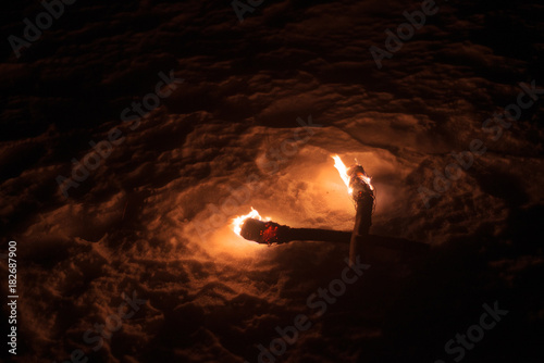 burning torch lights up the winter night fire alone dark lonely background natur Fototapet