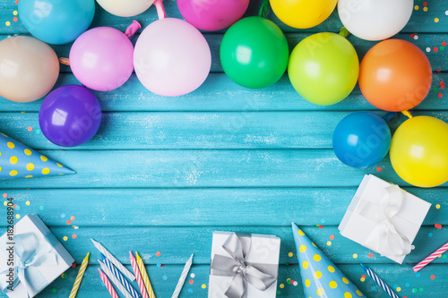 Holiday Frame With Colorful Balloons Gifts Confetti And Carnival Cap On Turquoise Table Top