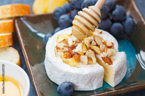 Brie cheese (camembert) with honey, nuts, baguette and fruit on a slate board.