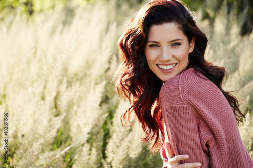 Fotografie, Tablou Portrait of a beautiful woman outdoors in a pink sweater