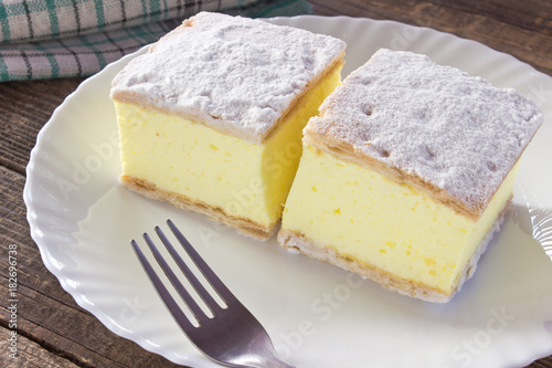 Obraz na plátne Cream pie with layers of puff pastry in plate on wooden table