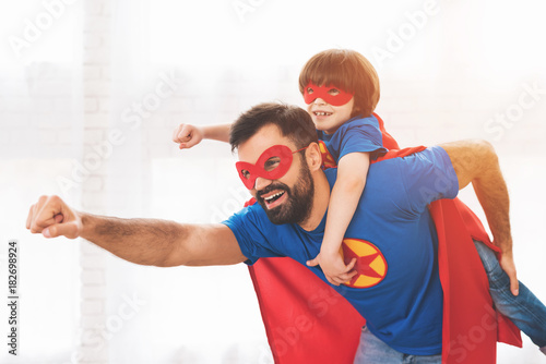 Carta da parati Father and son in the red and blue suits of superheroes