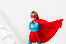 Little Girl Superhero In A Red Cloak And Mask On White Background.