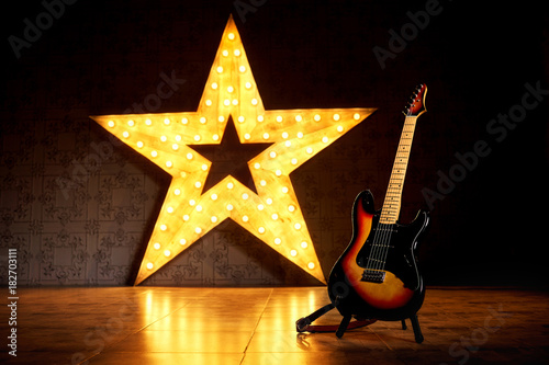 Valokuvatapetti An electric guitar on the background of a large electric star with luminous bulbs