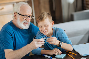 Pleasurable entertainment. Happy cheerful elderly man sitting with his grandson and holding a puzzle piece while collecting them together with him