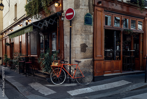 Cozy street with tables of cafe and old bicycle in Paris, France