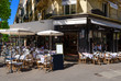 canvas print picture - Typical view of the Parisian boulevard with tables of brasserie (cafe) in Paris, France