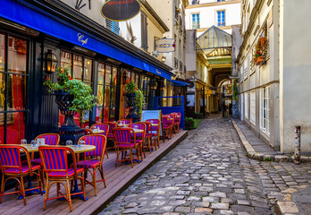 Fototapeta Paryż Cozy street with tables of cafe in Paris, France
