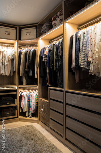 Fotomural  Luxurious walk in closet with lighting and jewelry display.
