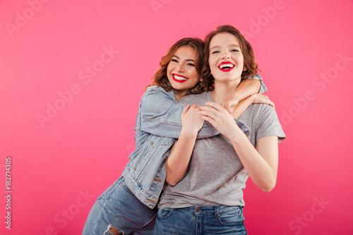 Happy two women friends hugging. Fototapeta