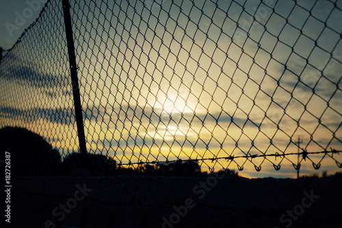 wire fence covering. A Fence Covering The Sunset Sky. Barbed Wire On Top. Symbolic Shot: Jail