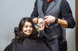 Professional male hairdresser cutting hair to a female client at design salon.