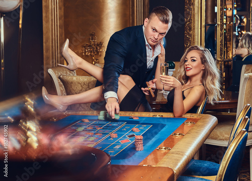 A man and woman play in a casino. плакат