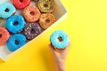 Woman Holding Tasty Glazed Donut And Box On Color Background