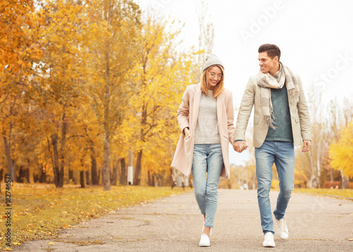 Young couple walking in park on autumn day Wallpaper Mural