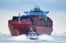 A Small Pilot Boat In Front Of A Huge Container Ship On The River Elbe, Germany