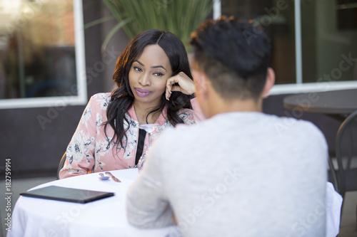 Fotografie, Obraz  Black female on a blind date with an asian male at an outdoor restaurant