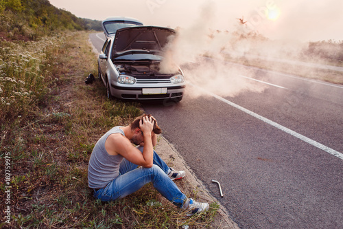 Fotografía  The car broke down, smokes from under the hood, the driver