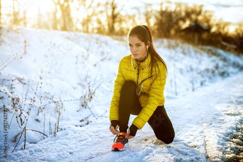 Poster Glisse hiver Young sportive healthy focused girl tying shoelaces in winter sportswear on snowy winter road with earphones in the sunny morning.