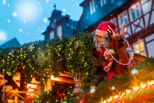 Christmas market spirit in Frankfurt, Germany. Celebrating xmas holidays. Lights, small houses at the market in the city center.