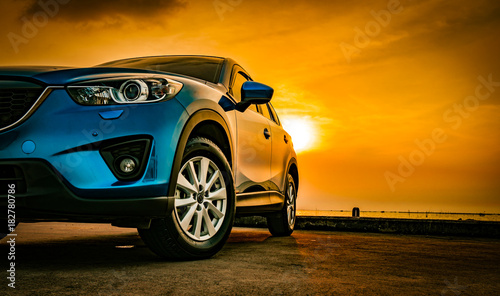 Blue compact SUV car with sport and modern design parked on concrete road by the sea at sunset. Environmentally friendly technology. Business success concept. - 182780786