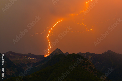 Spoed Fotobehang Onweer spectacular lightning bolt strike in mountain peak silhouette, orange sky, cloud