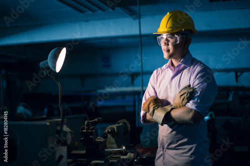 Portrait of young adult experienced industrial asian worker over industry machin Canvas Print