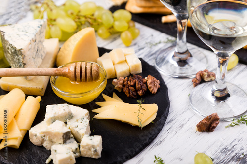 Foto op Aluminium Buffet, Bar Cheese plate. Assortment of cheese with walnuts, bread an honey on stone slate plate.