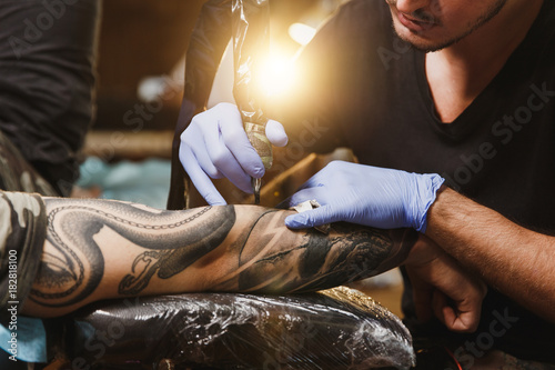 Photo Close up of professional tattooer artist doing picture on hand of man by machine black ink from a jar