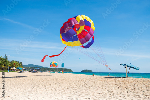 Beach recreation. Colorful parasail on tropical beach clear blue sky,travel destination.