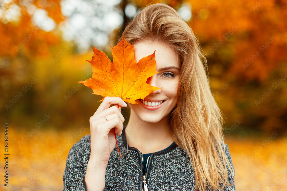 Fototapety, obrazy: Beautiful happy woman with a smile holds an autumn yellow leaf near the face