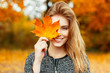 canvas print picture - Beautiful happy woman with a smile holds an autumn yellow leaf near the face