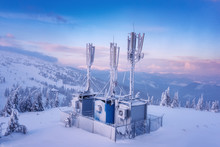 Cellular Base Station On The Snowy Winter Mountain Hill At Sunset Light