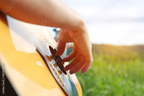 Fotografija  Close-up male hand playing on acoustic guitar outdoor with rays of sunlight