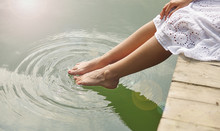 Women's Feet In The Water